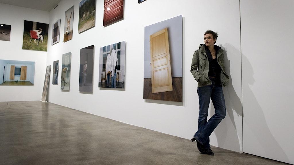 En kvinna står lutade mot en vägg i en konsthall med tavlor hängande på väggarna.
