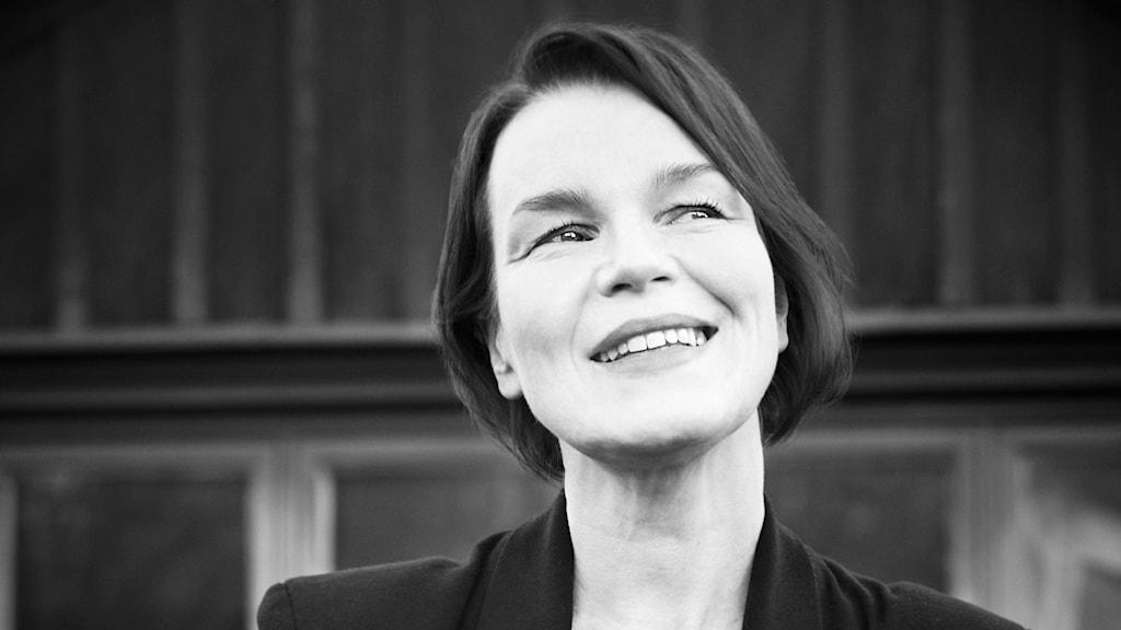 En svartvit bild på artisten Anna Järvinen. Hon har mörk page, ler och tittar lite upp till höger.