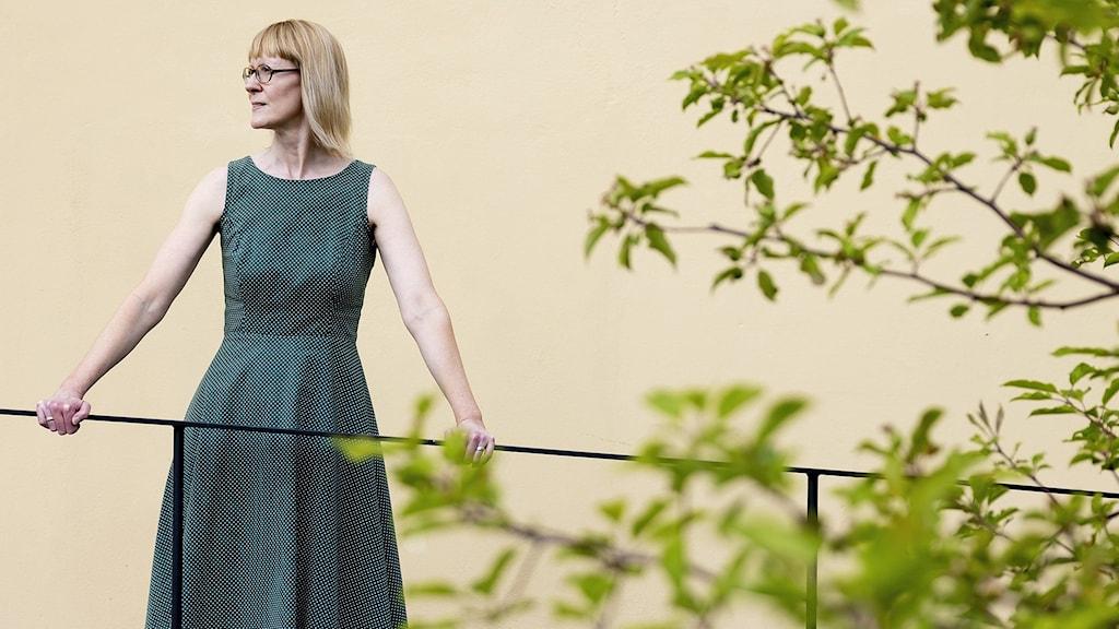 Jenny Björklund, klädd i grön klockad klänning med bara axlar, står vid ett smalt järnräcke. I förgrunden sträcker sig gröna kvistar med blad in.