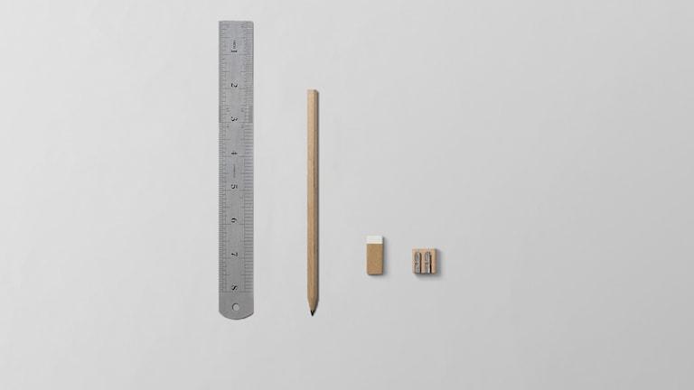 En stor linjal och en stor penna mot ett litet sudd och vässare.