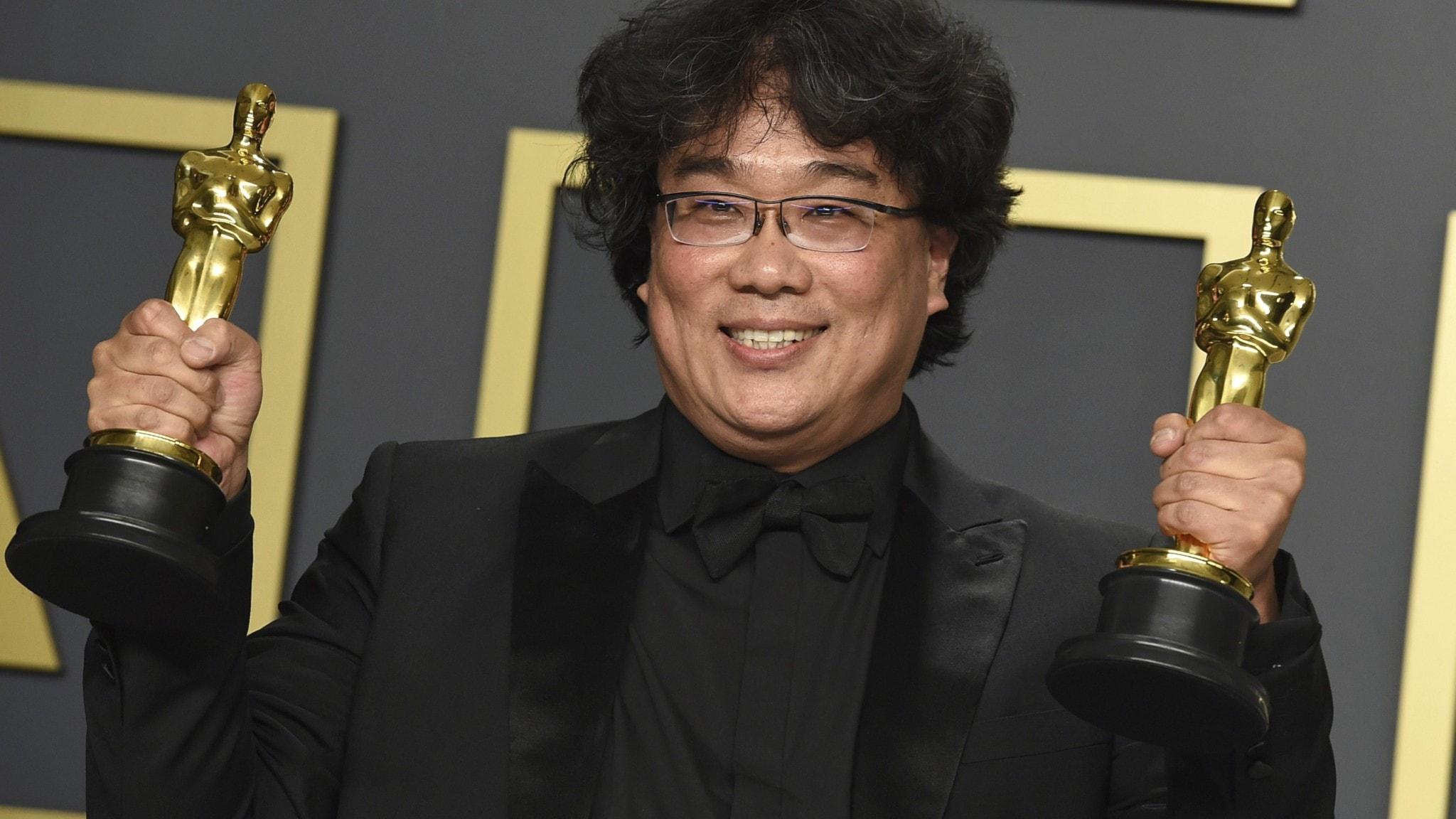 Bong Joon-Ho poserar med två av sina fyra Oscarsstatyetter.