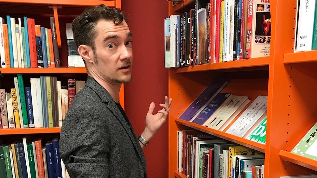 En man står vid en bokhylla och tittar frågande mot kameran.