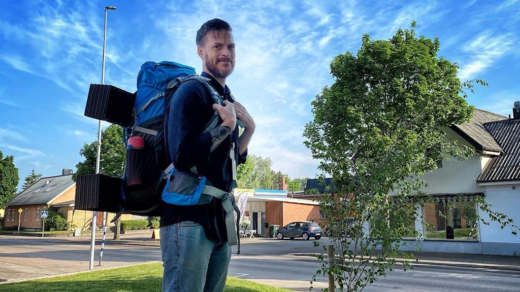 man med stor ryggsäck utomhus i fint väder