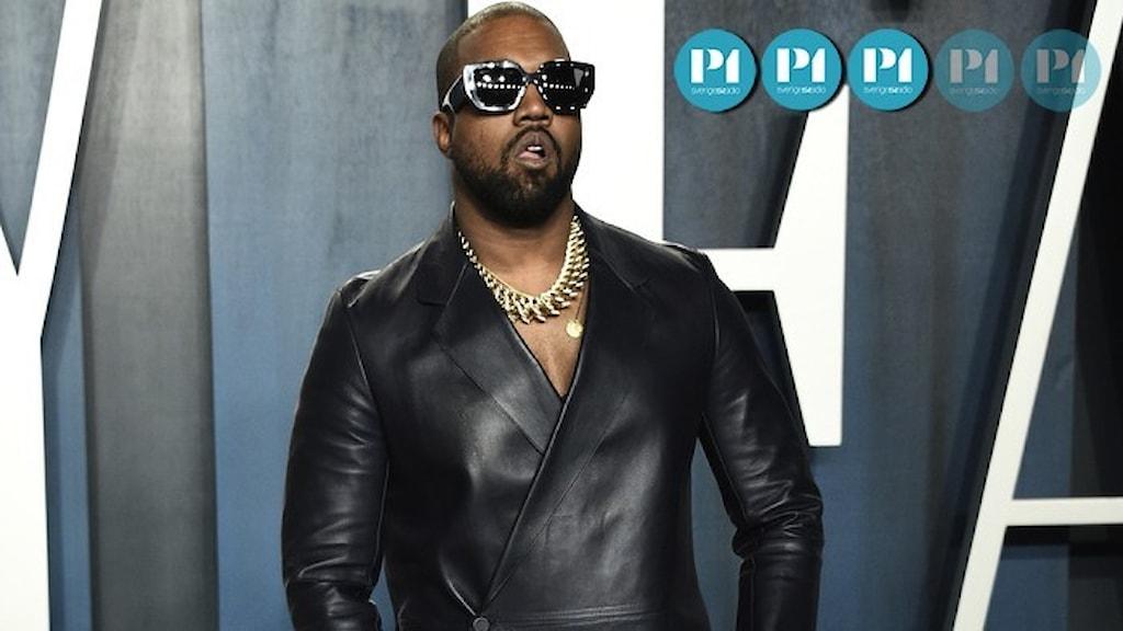 Artisten Kanye West i solglasögon och skinnklädsel under en premiär.