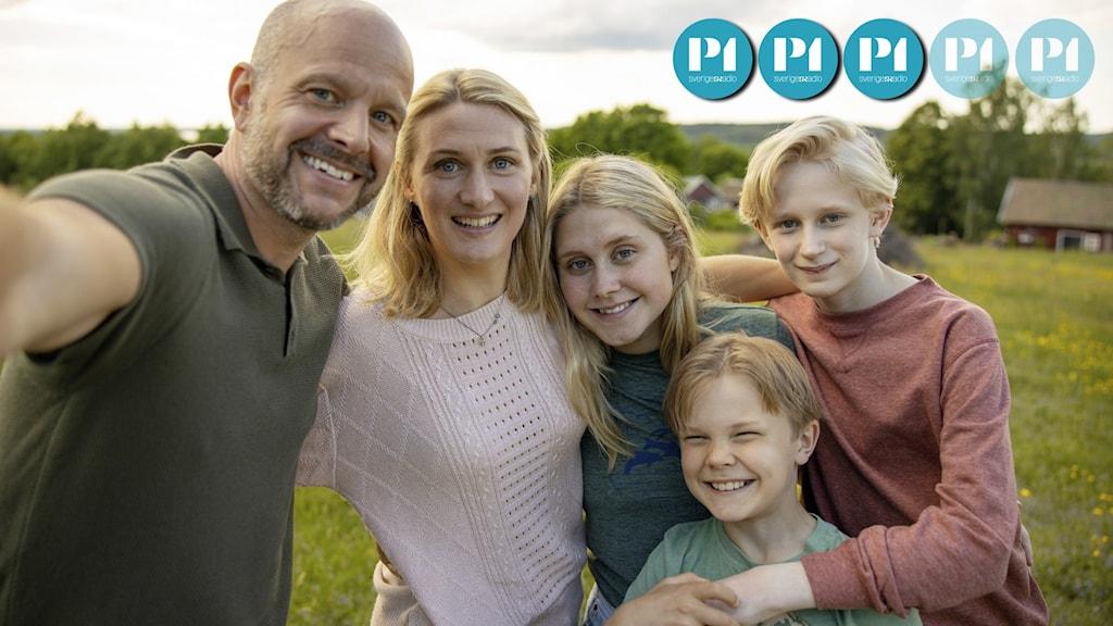 En familj med mamma, pappa och tre barn som tar en selfie.