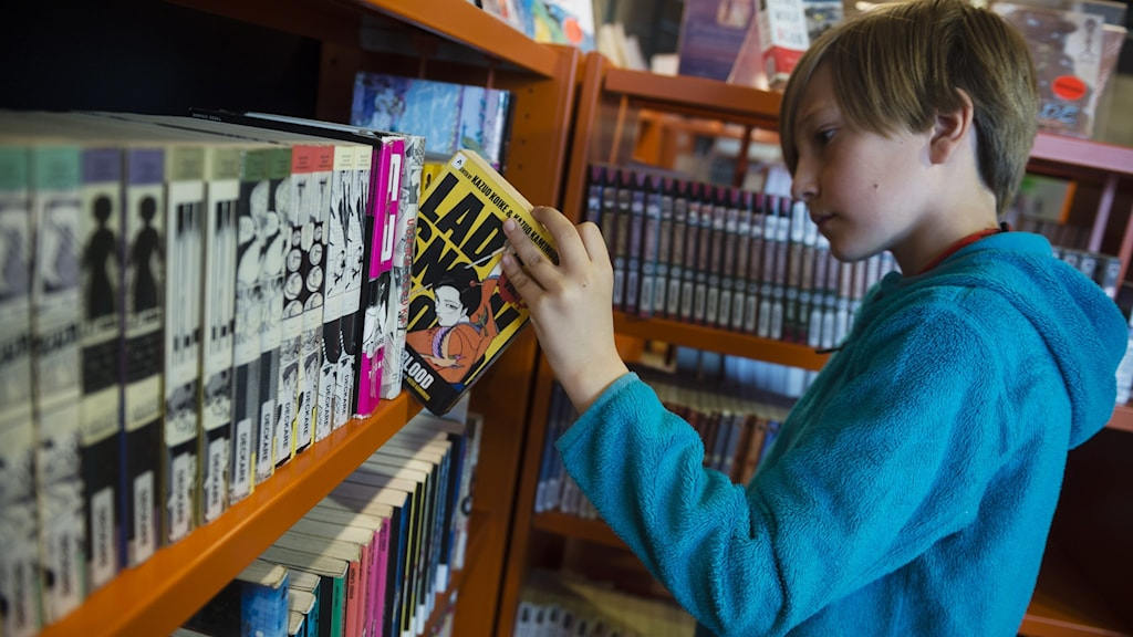 En pojke tar ut en bok ur en bokhylla på ett bibliotek.