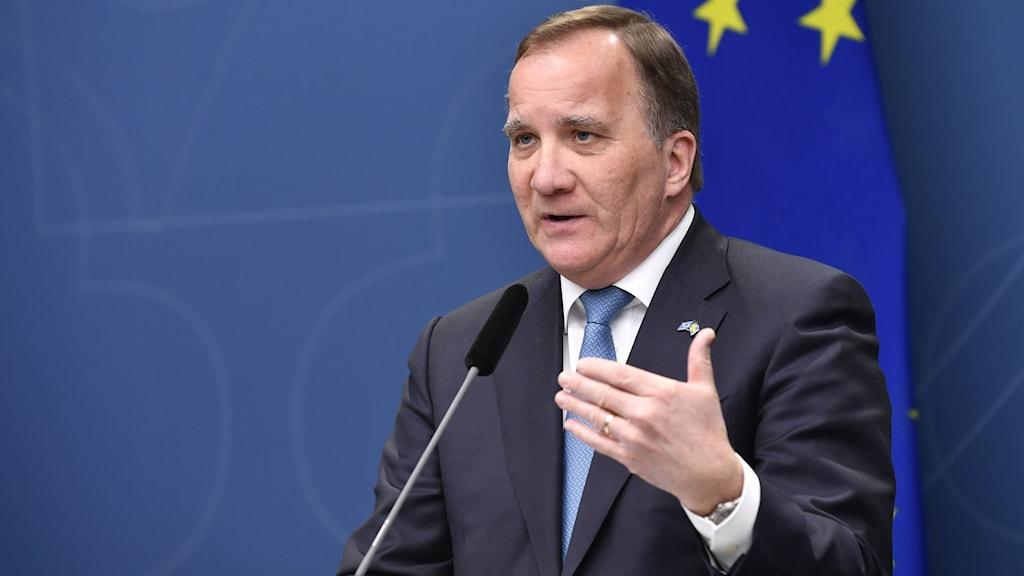 Statsminister Stefan Löfven (S) klädd i svart kostym och slips under en presskonferens. En EU-flagga syns i bakgrunden.