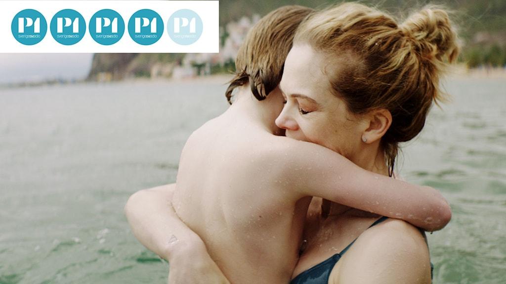 En mamma har lyft upp sin son ur havet och kramar honom hårt.