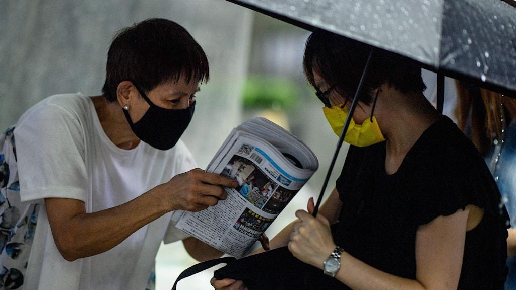 En person köper en tidning.