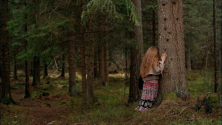 Kvinna i skogen bredvid träd.