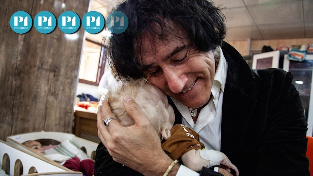 Patricio Galvez kramar sitt minsta barnbarn som ser blekt och utmärglat ut.