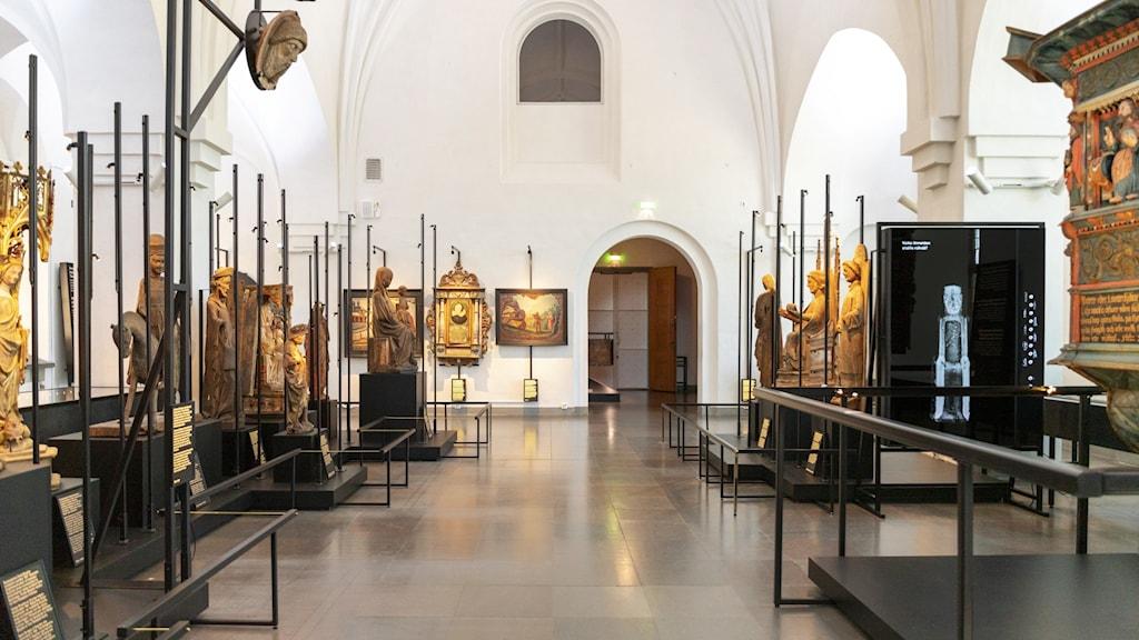 Utställningssal på Finlands Nationalmuseum med gamla träskulpturer på rad.
