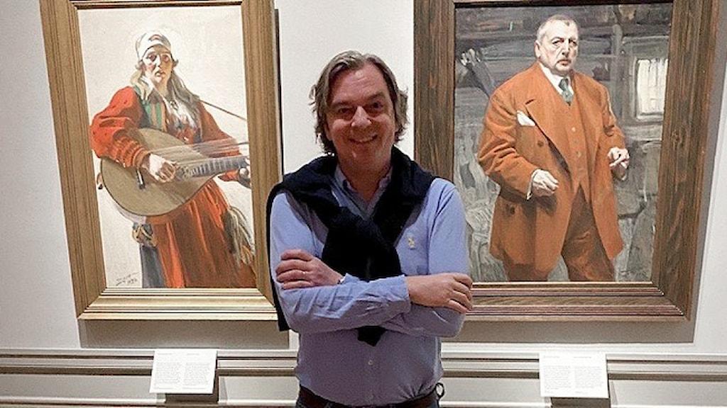 Porträtt av Carl-Johan Olsson, curator för Zorn-utställningen på Nationalmuseum, stående framför två tavlor av konstnären.