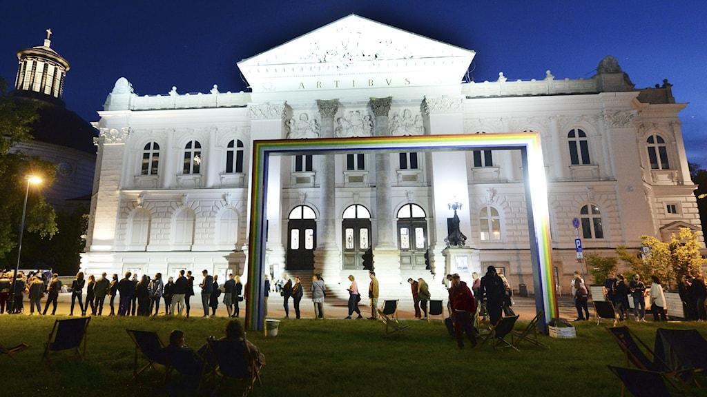 En vit fasad till ett av Polens konstmuseer. Människor köar utanför.