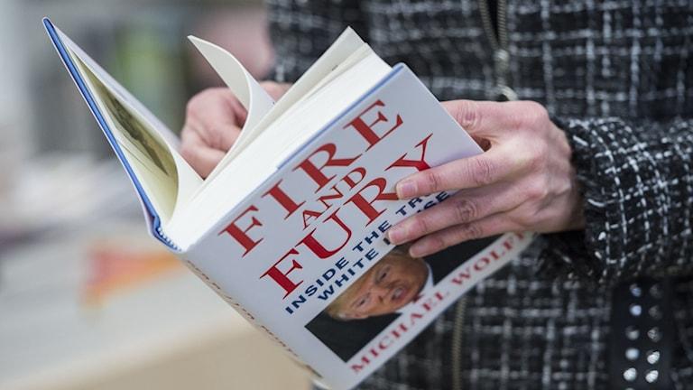 "En person läser Michael Wolffs ""Fire and fury""."
