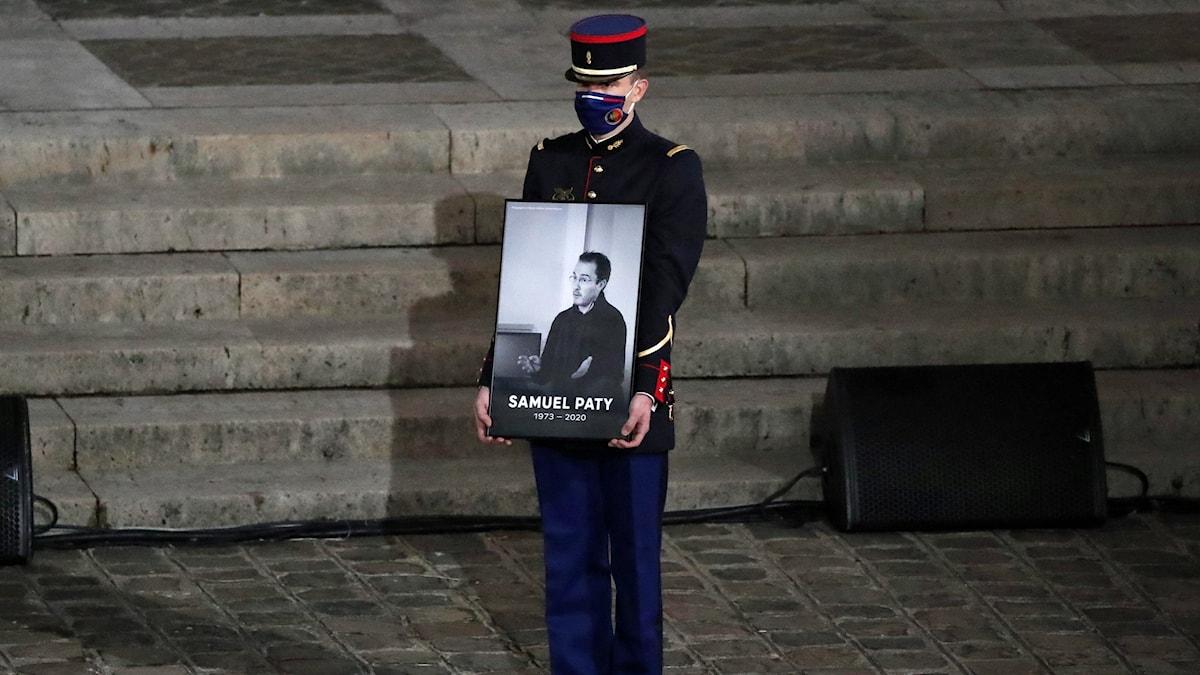 En gendarm håller ett portätt av Samuel Paty under en nminnesstund i oktober 2020