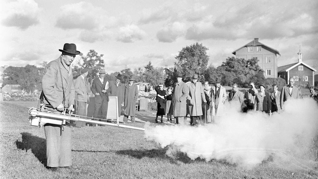 En man använder en ålderdomlig maskin på Experimentfältet 1954.