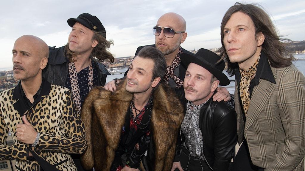 Rockbandet The Ark poserar på ett tak.