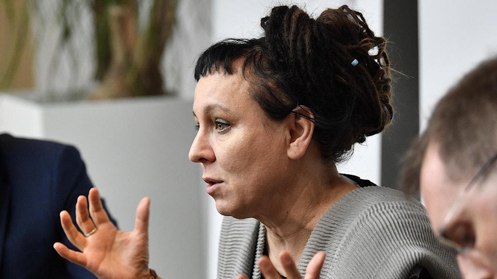 Den polska författaren Olga Tokarczuk sitter bakom ett bord och gestikulerar.