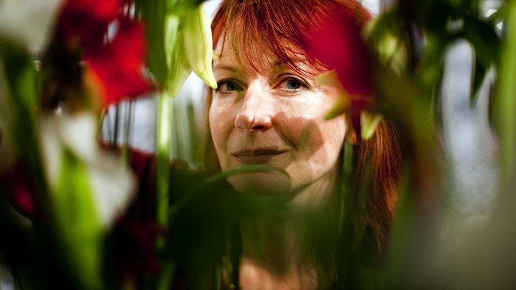 Författaren Inger Edelfeldt kikar fram genom gröna växter. Hennes hår är rött.