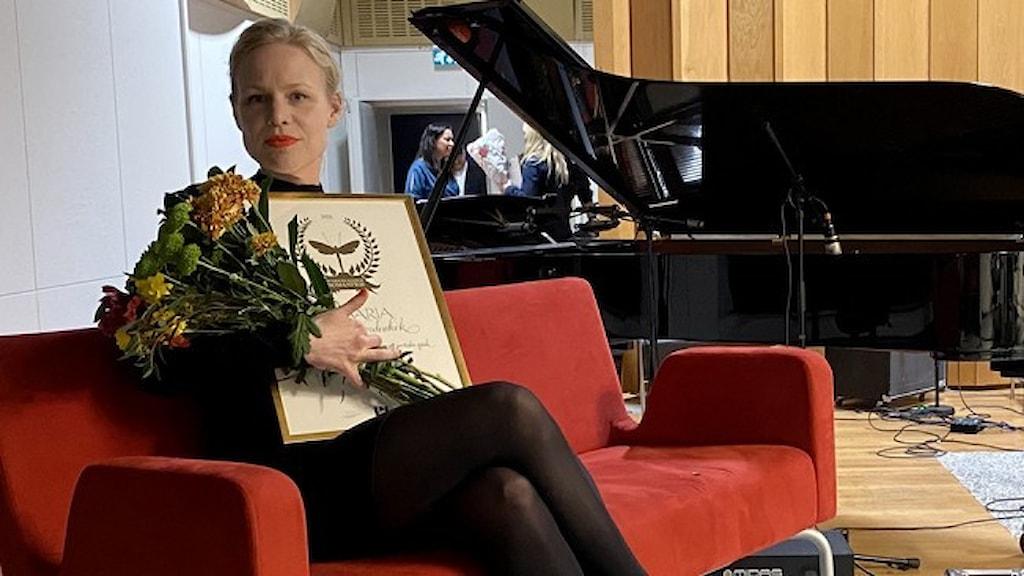Författaren Hanna Nordenhök vinnare av Sveriges radios romanpris 2021 med blommor och diplom, sittande i en röd soffa.