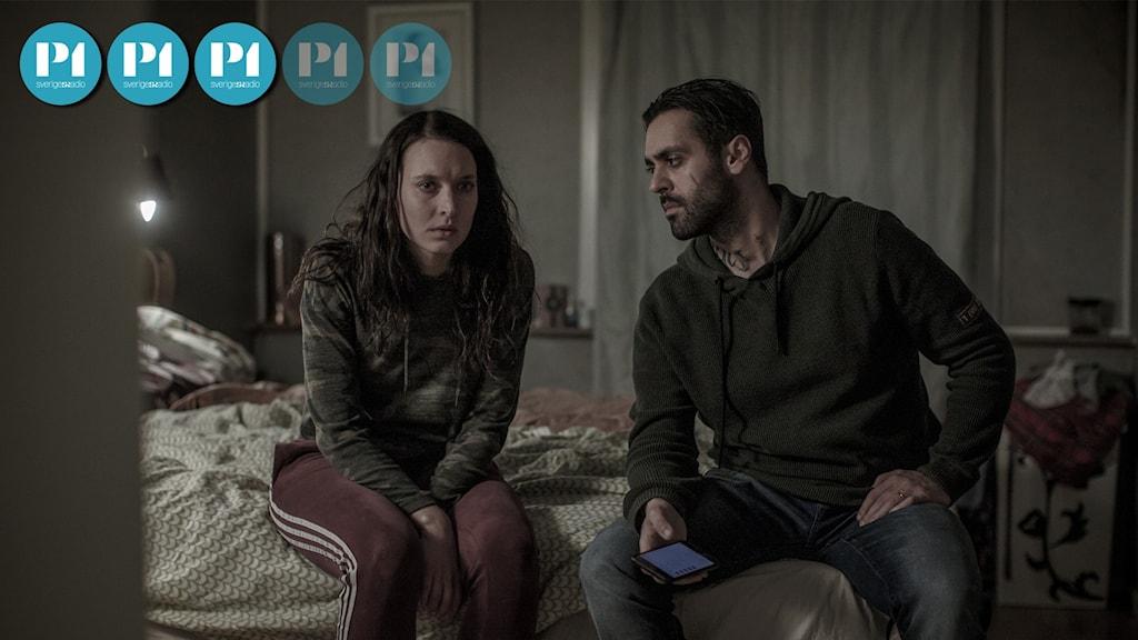 Två skådespelare sitter i en säng i SVT:s serie Snöänglar.