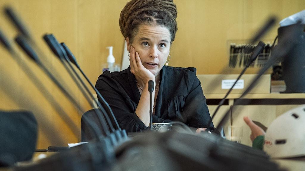 Kulturminister Amanda Lind (MP) sitter vid ett bord kantat med mikrofoner.