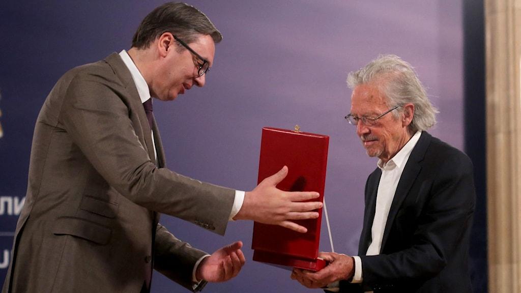 Serbiens president Aleksandar Vucic överräcker en utmärkelse till den österrikiska författaren och nobelpristagaren Peter Handke.
