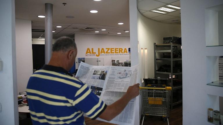 En man på al-Jaziras redaktion läser en tidning.