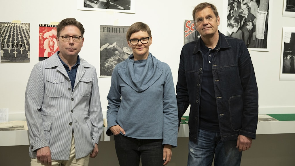Två män och en kvinna framför en vägg med fotografier
