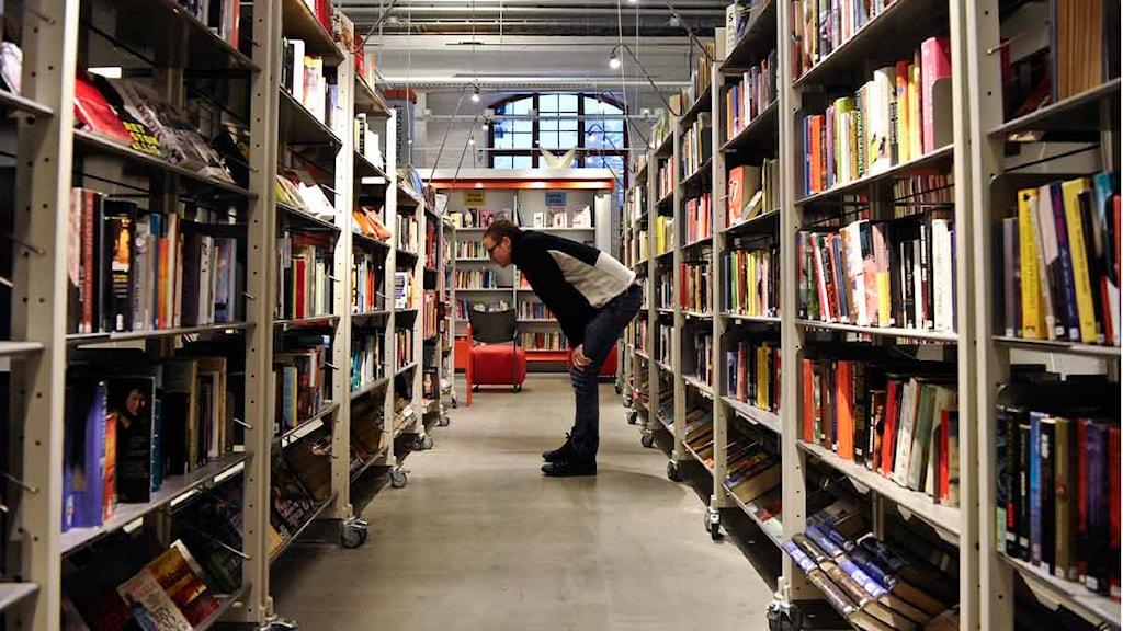 Bibliotek, läsning. Man tittar in i en bokhylla.