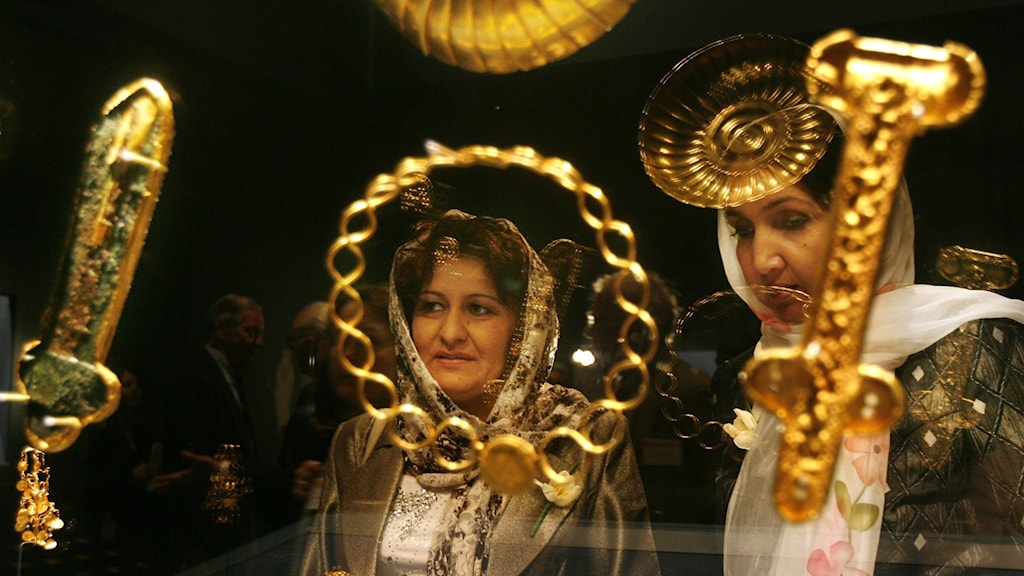 Två kvinnor tittar på guldföremål i en museimonter.