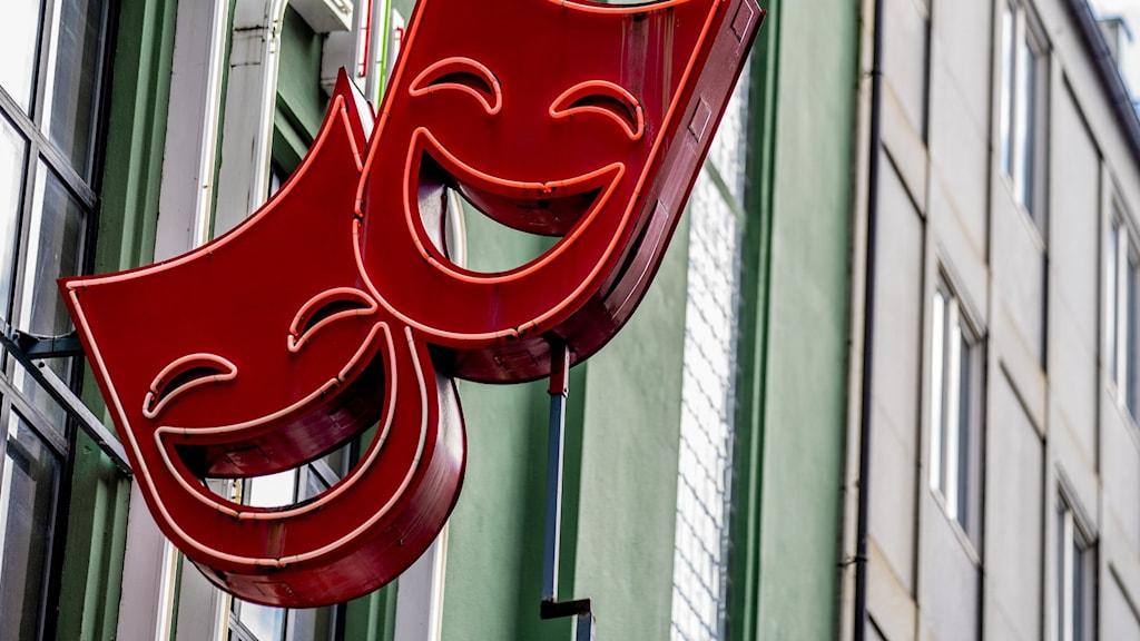 Två skrattande, röda figurer utanför en teater med grön fasad.