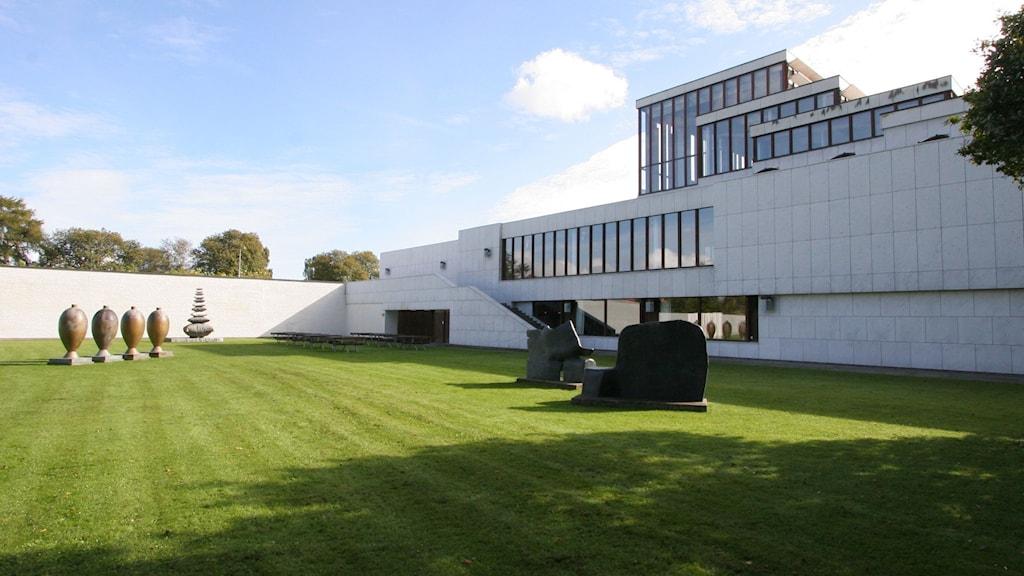 En vit byggnad framför en grön gräsmatta.