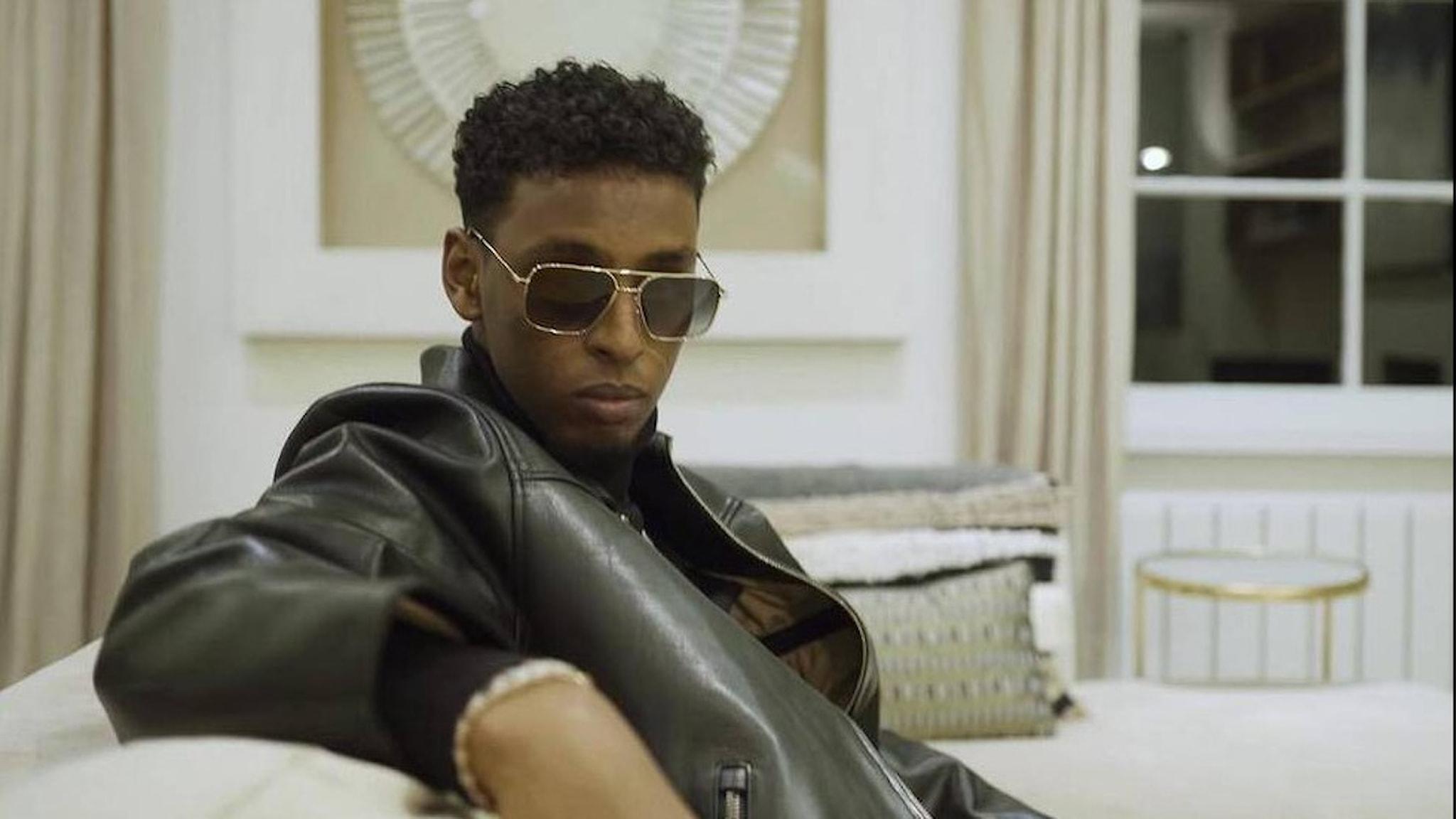 Artisten Yasin sitter i en soffa, han har solglasögon och en svart skinnjacka.