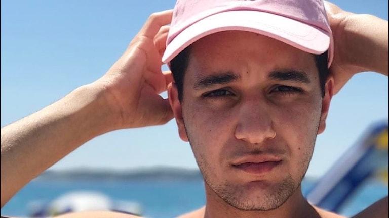 Thomas har en rosa keps på sig och man kan se havet bakom honom. Han har mörkt hår och ser rätt neutral ut.
