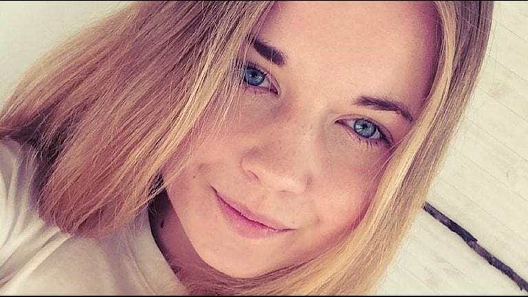 Anna är blond och tittar in i kameran. Hon ler med stängd mun.