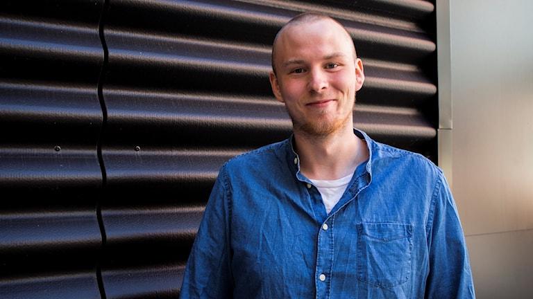 Jonas står i en blå jeansskjort mot en svart bakgrund. Ett mjukt ljus träffar hans ansikte från höger. Han ler och ser gullig ut.