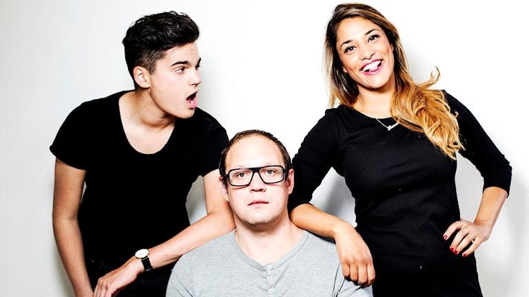 Oscar Zia, Jonatan Unge och Farah Erichsén står uppradade mot en vit vägg. Foto: Julia Lindemalm/SR