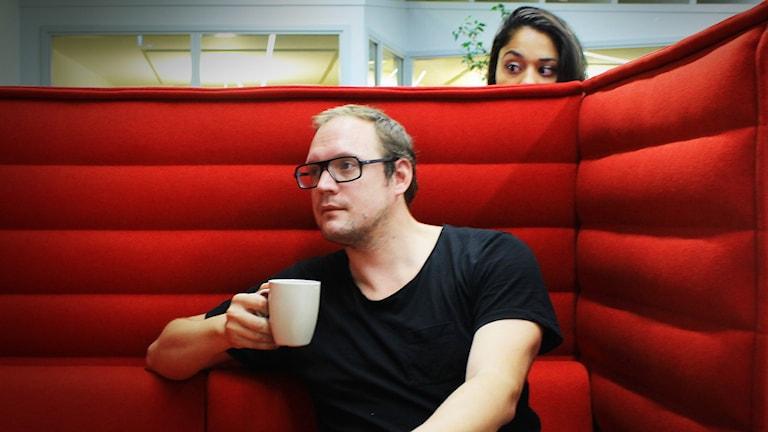 Jonatan sitter och dricker kaffe i en soffa. Farah spionerar på honom. Foto: Gustaf Widegård/SR