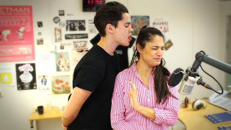 """Oscar står med händerna bakom ryggen och sträcker ut tungan mot Farah för att se """"lite sexig"""" ut. Farah sätter upp armen och ser äcklad ut. Bild tagen inne i studion. Foto: Gustaf Widegård/SR"""