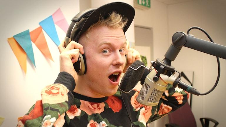 Anton står i studion med keps och hörlurar på huvudet. Han tittar in i kameran och gör en förvånad min. Foto: Gustaf Widegård/SR