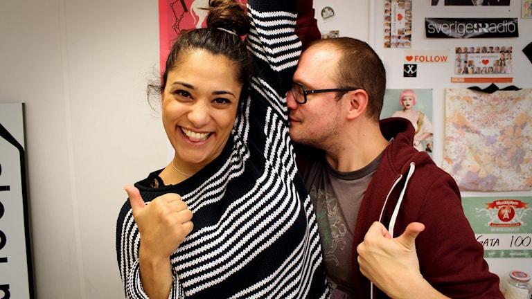 Farah ler stort, gör tummen upp och lyfter på armen. Jonatan gör också tummen upp samtidigt som han PREGAR in ansiktet i Farahs armhåla och luktar. Foto: Gustaf Widegård/SR