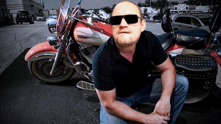 Originalbilden är på en man som sitter på huk framför en motorcykel. Vi har redigerat in Jonatan Unges huvud på originalet. Foto: Timothy Marsee/Flickr/CC BY-SA 2.0/Gustaf Widegård/SR