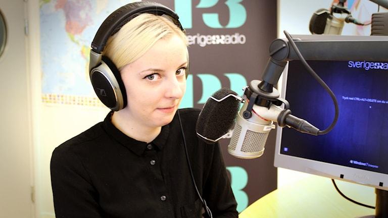 Torsdagsdejten Alice ler i smyg och sneglar mot kameran. Hon sitter i studion med hörlurar på huvudet. Foto: Gustaf Widegård/SR