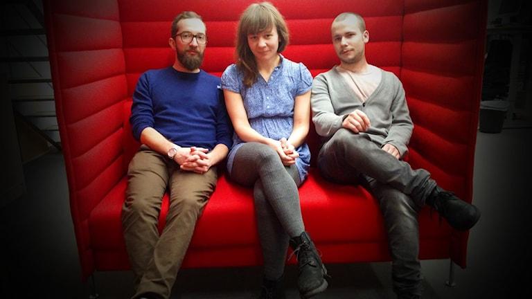 Tre personer sitter i en röd soffa med höga kanter. Från vänster till höger: Marcel, Sofia och Viktor. Alla sitter men knäppta händer och ser allvarliga ut. Foto: Gustaf Widegård/SR