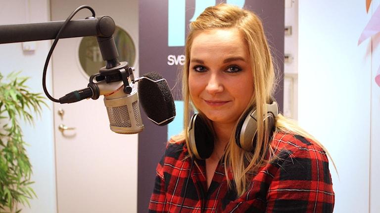 Veckans singel Emilija har på sig en rödrutig flanellskjorta och långt blont hår. Hon tittar in i kameran och ler lite.
