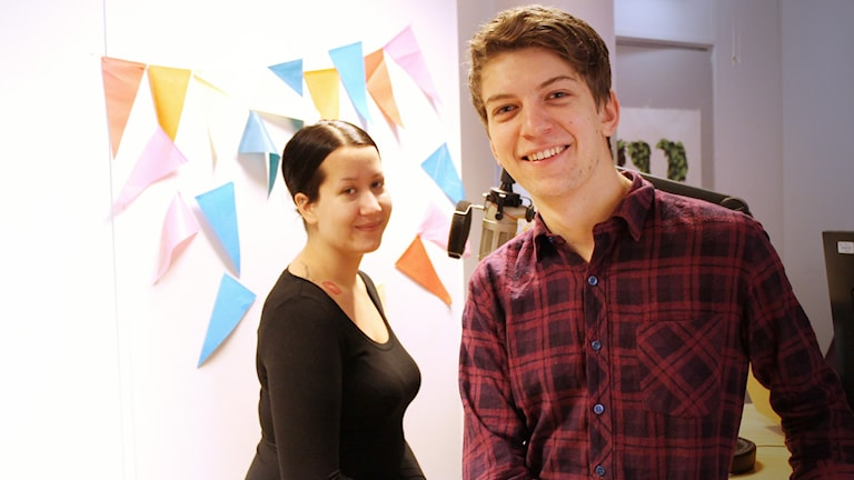 Till vänster i bild är Layla med svart hår och svart topp. Till höger står Rasmus i en rödrutig skjorta och ler.