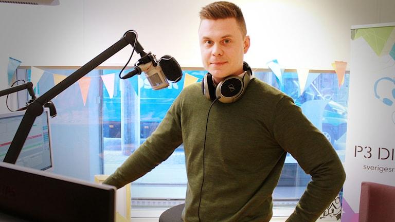 Rekryteraren Patrik Gustavsson står framför mikrofonen i en mörkgrön kofta och tittar in i kameran.