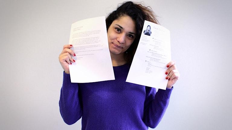 Farah håller upp ett CV och ett personligt brev bredvid sitt ansikte. Hon ler lite och tittar in i kameran.